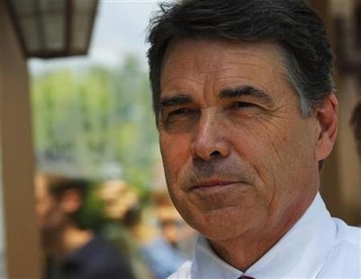 Republican presidential candidate Texas Governor Rick Perry leaves a campaign stop at Harvey's Bakery and Coffee Shop in Dover