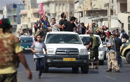 Libyan rebel fighters celebrate as they drive through Tripoli's Qarqarsh district
