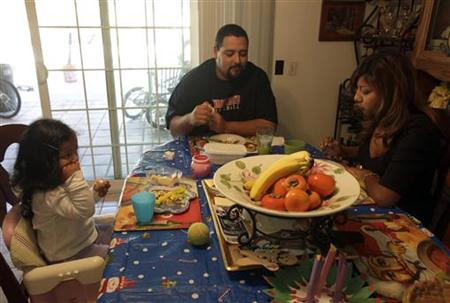 Thelma Zambrano eats lunch with her husband Jesse Torres and daughter Vida Torres, 2, at their home in Santa Ana, California