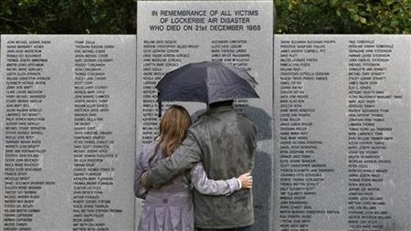 A couple shelters from the rain under an umbrella as they look at the main headstone in the Lockerbie air disaster memorial garden in Locker