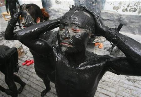 Visitors cover their bodies with black mud at a tourist resort in Daying County
