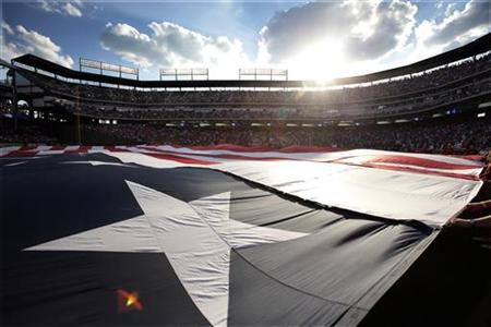 American flag used at the recent All-Star game is unfurl during the national anthem before the Texas Rangers and Toronto Blue Jays MLB Ameri