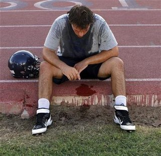 McClintock High School Chargers football player Joe Sanford takes a break from practice after feeling light-headed in Tempe