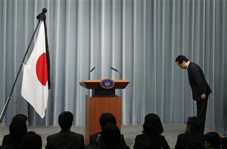 Japan's Prime Minister Naoto Kan bows to the national flag as he arrives for a news conference at his official residence in Tokyo