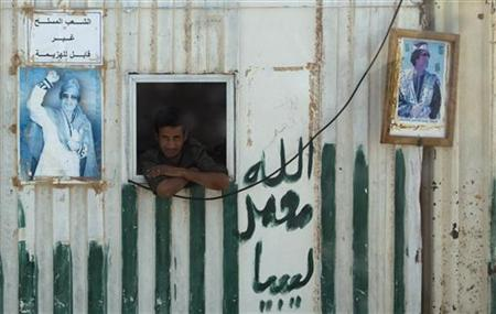 A soldier looks out of a window at a checkpoint on the road to Sirte