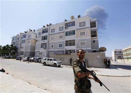 Rebel fighters secure an area during fighting in Abu Slim in Tripoli