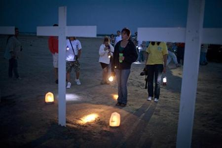 Participants gather around crosses honoring the workers who died on the Deepwater Horizon oil platform, during a service marking the one-yea