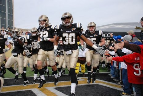 Western Michigan University players storm out of the tunnel at Waldo Stadium in 2010.
