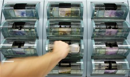 A bank clerk removes 200 Swiss franc banknotes out of a money counter in a bank in Zurich