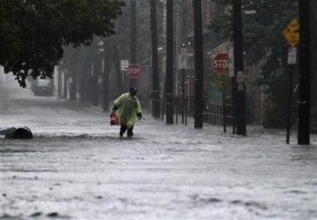 A pedestrian walks through a flooded street at Hoboken
