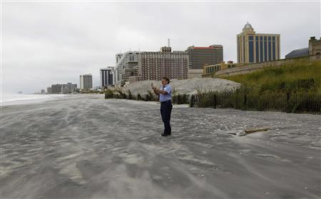 A worker at the Trump Casino in Atlantic City takes a picture of the coastline near the boardwalk following Hurricane Irene