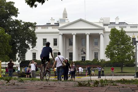 Tourists walk by the White House the morning after Hurricane Irene passed by Washington