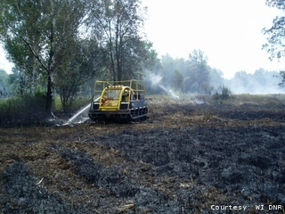 The DNR continues to extinguish a forest fire near Peshtigo in Marinette County, Aug. 27, 2011.