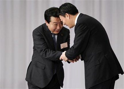 Japan's Finance Minister Yoshihiko Noda, who was chosen as the new leader of the ruling Democratic Party of Japan, shakes hands with Trade M