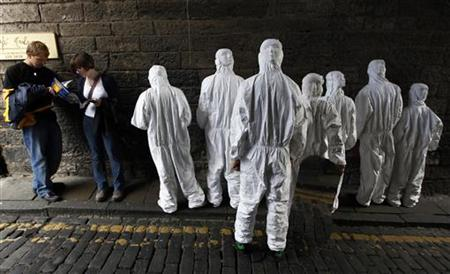 "Performers from ""The Gift of the Gorgon"" show stand together in a dark alleyway in the Royal Mile to promote their show during the Edinburgh"