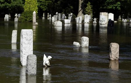 Water flows past flooded gravestones in the town of Totowa