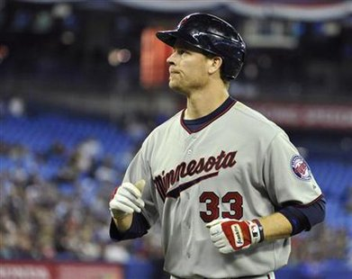 Twins batter Justin Morneau runs back to the dugout after flying out during their MLB American League game in Toronto