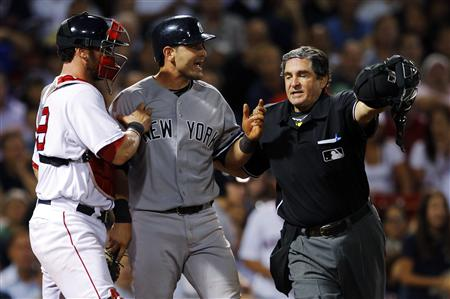 New York Yankees' Cervelli is held back by Boston Red Sox's Saltalamacchia and home plate umpire Capuano after getting hit by a pitch during
