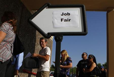 People wait in line to enter a job fair at the Phoenix Workforce Connection in Phoenix