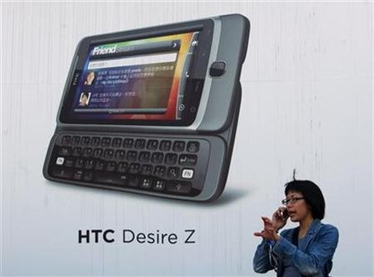 A woman talks on her mobile phone in front of a HTC advertisement in Taipei