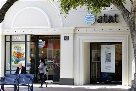 The white Apple iPhone 4 and iPad 2 are advertised in the window of an AT&T cellular store in Los Angeles