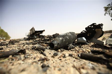 Parts of a destroyed missile lie on the ground near a truck on the road to Bani Walid