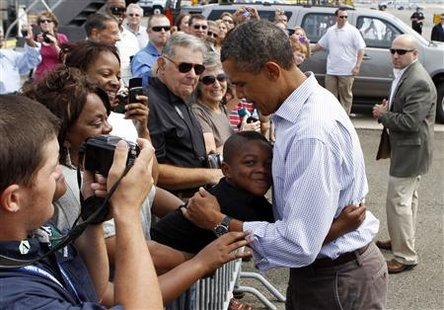 U.S. President Barack Obama gets a hug from a boy upon his arrival in Newark, New Jersey