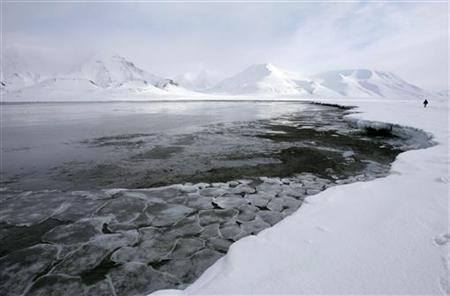 Ice breaks away from a frozen coastline near the Norwegian Arctic town of Longyearbyen