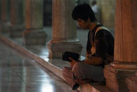A Muslim man reads the Koran at the Al Azhar mosque in Cairo