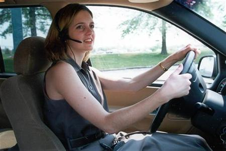"An unidentified woman uses a ""hands-free"" headset to make her driving easier and safer. Proposals to.."