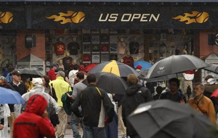 Patrons wait near playing courts after rain delayed competition in the U.S. Open tennis tournament in New York