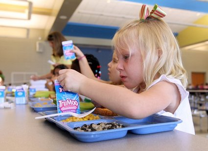 A child drinking milk in a school cafeteria
