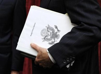 Congressional Super Committee member Sen. Jon Kyl (R-AZ) carries a binder titled Budget Policy Options as he departs the inaugural meeting,
