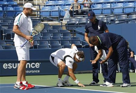 David Ferrer of Spain and Andy Roddick of the U.S. of the examine a spot on the court where water is coming from below the surface at Louis