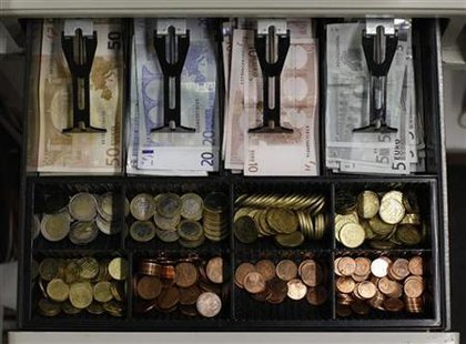 Euro banknotes and small coins are pictured in open cash register in Olching