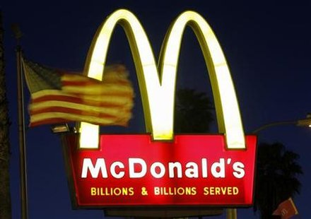 A U.S. flags flutters in the wind in front of a sign for a McDonald's restaurant in Los Angeles