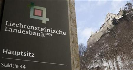 A sign marks the entrance of the headquarters of the Liechtensteinische Landesbank bank as Vaduz Castle is seen beside in the country's capi
