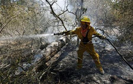 Texas firefighter Zdroj fights a hot spot in the woods near Bastrop