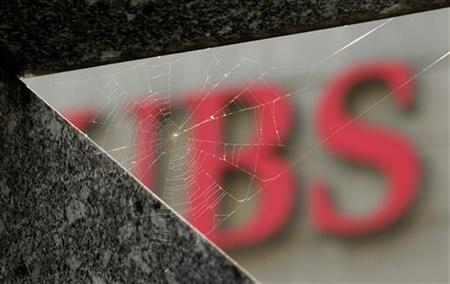 A cobweb is seen in front of the logo of Swiss bank UBS in Zurich