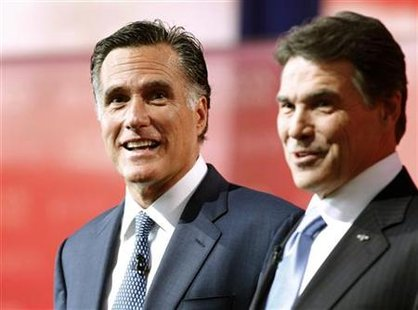 Mitt Romney stands with Rick Perry onstage during a photo opportunity before the Reagan Centennial GOP presidential primary debate in Simi V