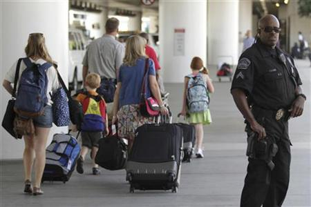 Travelers walk past a police officer at Los Angeles International Airport