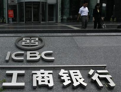 People walk past a company logo of the Industrial and Commercial Bank of China (ICBC) outside one of its branches in Beijing