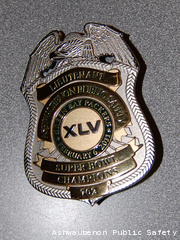 An Ashwaubenon Public Safety badge commemorating the Green Bay Packers' Super Bowl XLV championship is seen.