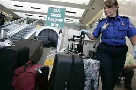TSA worker loads suitcases at luggage security screening station at Los Angeles International Airport