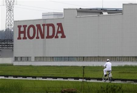 A worker rides a bicycle past a Honda auto parts manufacturing plant in Foshan, Guangdong province