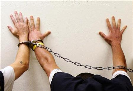 Prisoners place their hands on a wall as they are brought to jail by Orange County sheriff's deputies in Fullerton