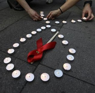 Activists distribute red ribbons and light up candles as they commemorate victims of the Human Immunodeficiency Virus, or HIV, during a flas