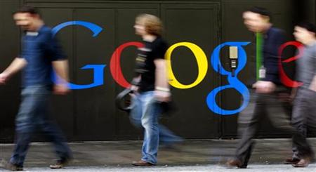 People walk past a logo next to the main entrance of the Google building in Zurich
