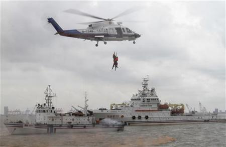 Rescuers dangle from a helicopter during a maritime and aerial joint emergency drill at Waigaoqiao dock in Shanghai