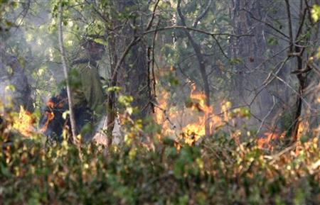 A U.S. forestry worker watches a controlled burn created to seal off a wildfire's path as it approaches a house near Bastrop, Texas